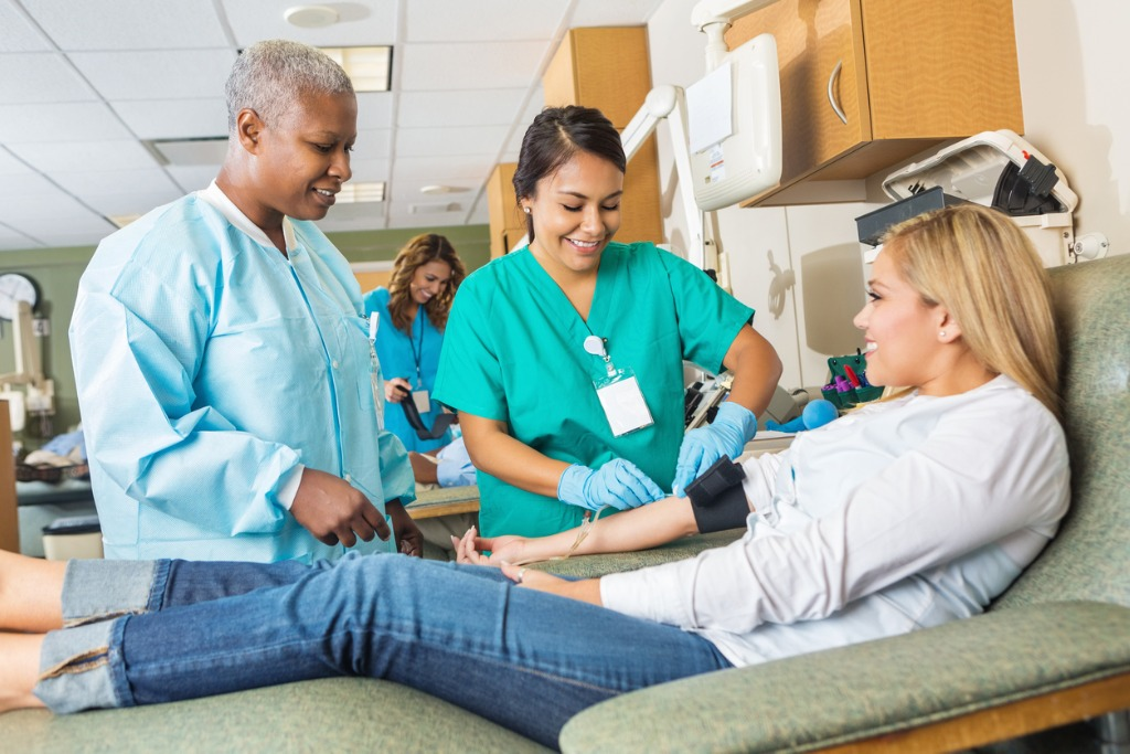 nurse-learning-to-assist-patient-donating-blood-in-hospital-picture-id520238991